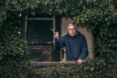 Senior man with a gun protecting property Stock Image