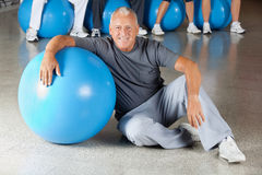 Senior man with gym ball in fitness. Happy senior man with gym ball in fitness center Stock Photo