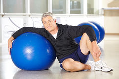Senior man with gym ball in fitness center. Happy senior man with gym ball in fitness center doing back training Stock Image