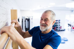 Senior man in gym exercising on wall bars. Royalty Free Stock Photography