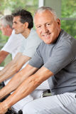 Senior man in gym riding bicycle Royalty Free Stock Photo