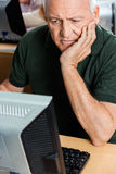 Senior Man With Hand On Chin Using Computer In Classroom Royalty Free Stock Photography