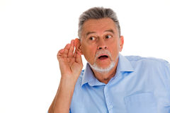 Senior man with hand to ear listening Stock Photo