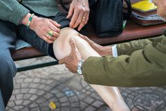 Senior man hands doing massage on old woman pain legs on street.  Royalty Free Stock Images