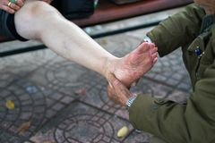 Senior man hands doing massage on old woman pain legs on street.  Royalty Free Stock Photography