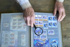 Senior man hands hold magnifier and stamp album with postage stamps collection, space theme, wooden background.  stock images