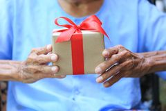 Senior man hands holding gift box with red ribbon for Christmas royalty free stock photography