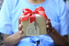 Senior man hands holding gift box with red ribbon and house mode stock images