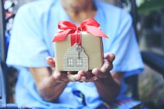 Senior man hands holding gift box with red ribbon and house model with keys, Gift new home and Real estate concept stock images