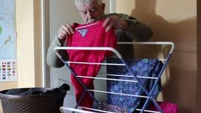 Senior man hanging washing on a rack to dry. stock video