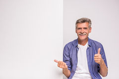 Senior man. Happy senior man is holding blank placard on white background royalty free stock image