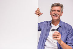 Senior man. Happy senior man is holding blank placard on white background and drinking coffee stock photos