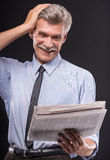 Senior man. Happy senior is reading newspaper on dark background stock image