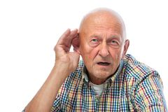 Senior man hard of hearing. Senior man cupping his ear having difficulty hearing Stock Photos
