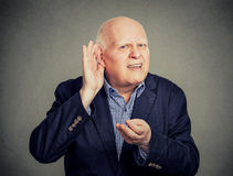 Senior man, hard of hearing, placing hand on ear asking someone to speak up Royalty Free Stock Photo
