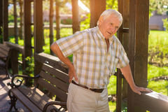 Senior man has backache. Elderly male outdoors. Disease of spine. Strong pains during movement Stock Photo