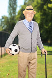 Senior man with hat holding a soccer ball in a park Stock Images