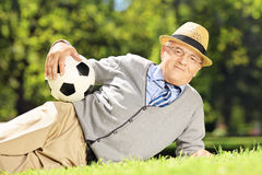 Senior man with hat lying on a grass and holding a ball in a par Royalty Free Stock Photography