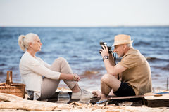Senior man in hat photographing smiling woman with instant camera at beach Stock Photography