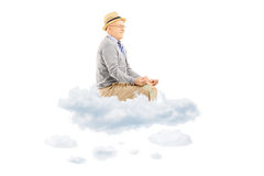 Senior man with hat seated on clouds meditating Royalty Free Stock Photos