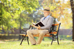 Senior man with hat sitting on a bench and reading a novel, in a. Senior man with hat sitting on a wooden bench and reading a novel, in a park Royalty Free Stock Images