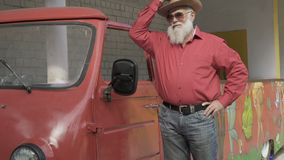 Senior man in hat and sunglasses poses near vintage car stock footage