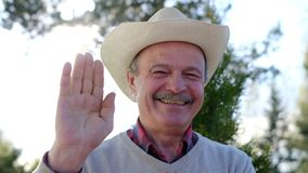 Senior man in hat waving his hand. Say hello bye. Positive human emotions, facial expressions. Senior spanish man in hat waving his hand. Father greeting his stock footage