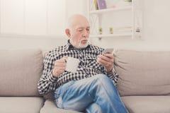 Senior man using smartphone while drinking coffee Royalty Free Stock Image