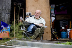 A senior man having a break on an allotment, reading a newspaper Stock Image