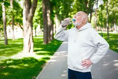 Senior man is having break, drinking water. Senior male runner is having break, drinking water while jogging in park Royalty Free Stock Photo