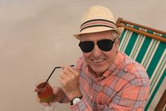 Senior man having cocktail drink while relaxing in a sun lounger. Front view of active senior man having cocktail drink while relaxing in a sun lounger at the stock photo