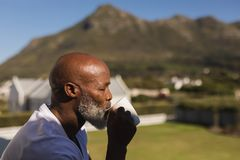 Senior man having coffee on the balcony. Side view of a handsome senior African American man drinking a cup of coffee on the balcony at home royalty free stock image