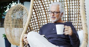 Senior man having coffee while reading a book 4k stock footage