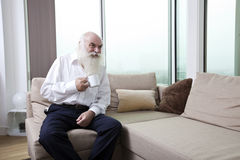 Senior man having coffee while sitting on sofa in apartment Royalty Free Stock Image