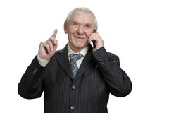 Senior man having conversation on his phone. Clarify details, one more thing. White isolated background Stock Photography