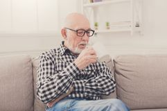 Senior man having cup of coffee in living room. Senior man having rest with cup of coffee or tea in living room, copy space stock photography
