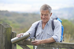 Senior Man Having Drink From Flask Whilst On Walk Stock Images