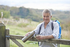 Senior Man Having Drink From Flask Whilst On Walk. Portrait Of Senior Man Having Drink From Flask Whilst On Walk Royalty Free Stock Image