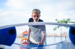 Senior man having fun at the arcade. Active lifestyle Royalty Free Stock Images