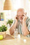 Senior man having headache. Pensioner suffering from migraine, holding head with closed eyes, taking painkiller at home Stock Photos