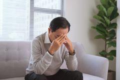 Senior man having headache while sitting on couch at home. royalty free stock photos