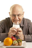 Senior man having a healthy breakfast. Isolated on white Royalty Free Stock Photography