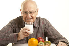 Senior man having a healthy breakfast. Isolated on white Royalty Free Stock Photos