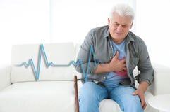 Senior man having heart attack. On sofa stock images