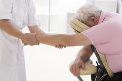 Senior man having massage in a massage chair Stock Photos