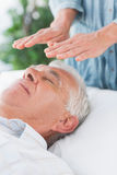 Senior man having Reiki treatment Royalty Free Stock Photos