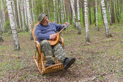 Senior man is having rest in birch forest Stock Photography