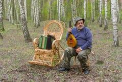 Senior man is having rest in birch forest Stock Photos