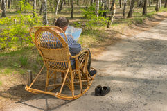 Senior man is having rest in coniferous forest Royalty Free Stock Photo