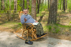 Senior man is having rest in coniferous forest Stock Photos
